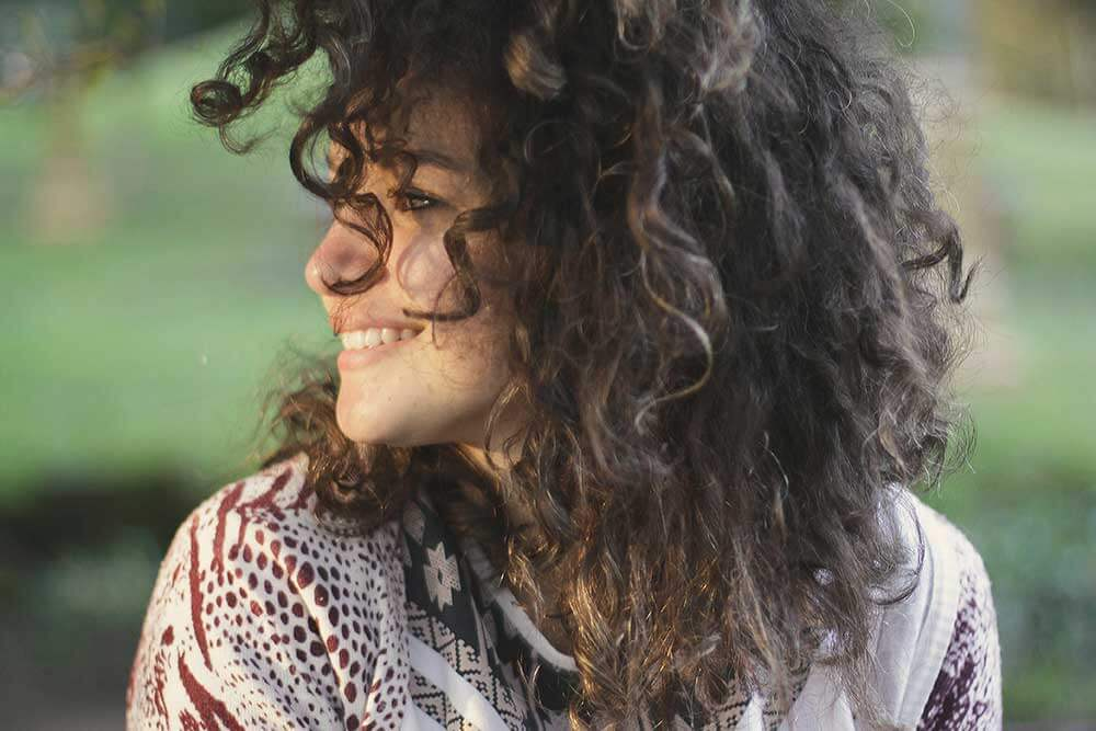 young woman with curly hair smiling