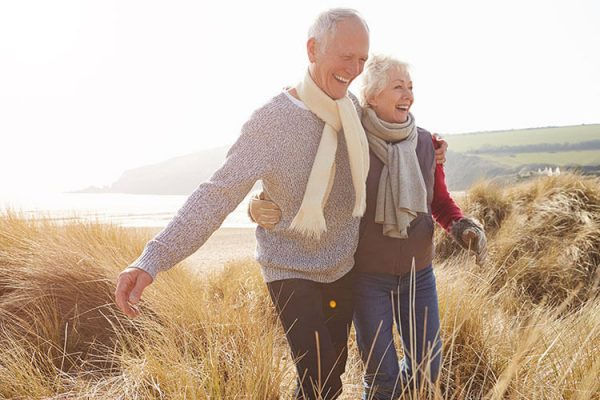 Older couple with their arms around each other laughing and walking through a field