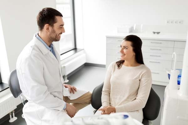 Dentist standing and speaking to young woman who is sitting in an office chair
