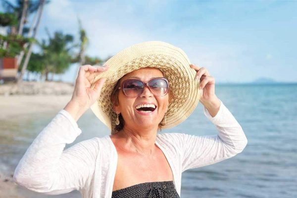 A woman on the beach smiling and holding her hat on her head