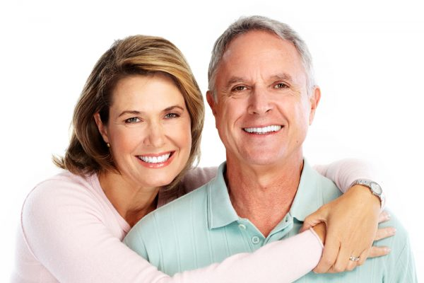 An older woman with her arms around her husband and smiling