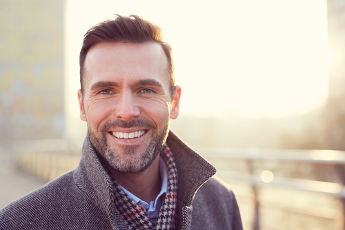 A man on a rooftop smiling with the sun shining behind him